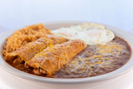 Generous serving meal of a hearty pair of breakfast enchiladas combined with refried beans, rice, and eggs. Stock Photo
