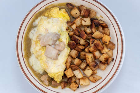Overhead view of generous serving meal of a hearty chili verde covered in green sauce combined with eggs and potatoes.