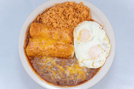 Overhead view of generous serving meal of a hearty pair of breakfast enchiladas combined with refried beans, rice, and eggs.