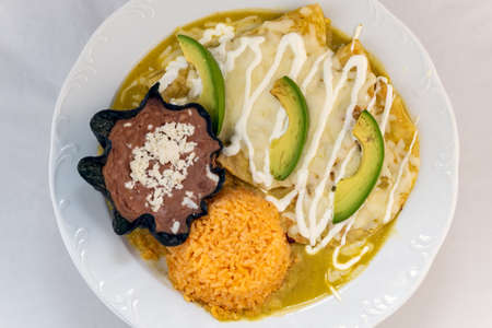 Overhead view of enchiladas Suizas served with rice and tortilla chip bowl refried beans looks and tastes appealing.