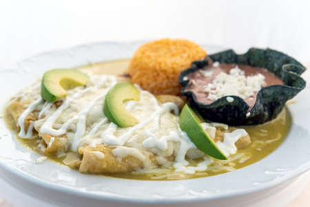 Enchiladas Suizas served with rice and tortilla chip bowl refried beans looks and tastes appealing. Stock Photo