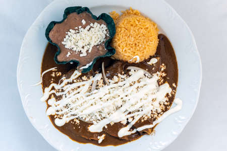 Overhead view of enchiladas mole served with rice and tortilla chip bowl refried beans looks and tastes appealing.