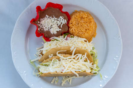 Overhead view of hardshell tacos served with rice and tortilla chip bowl refried beans looks and tastes appealing.