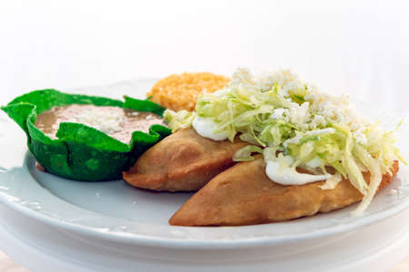 Fried Quesadillas served with rice and tortilla chip bowl refried beans looks and tastes appealing.