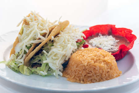 Hardshell tacos served with rice and tortilla chip bowl refried beans looks and tastes appealing.