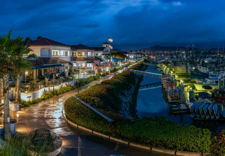 Ventura Harbor Village boardwalk is reflective and wet from the early morning rain with rain clouds reflected in harbor water.