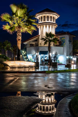 Ventura Harbor Village carousel tower reflected in a puddle of water in the shiny and wet parking lot from morning rain.