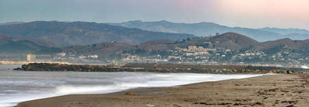 Ventura coastline of sandy beachs nestled against rolling hilltops with rock jettys in between.