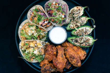 Overhead view of delicious appetizer sampler plate with chicken and steak tacos, poppers, and buffalo wings makes the mouth water and the stomach growl.