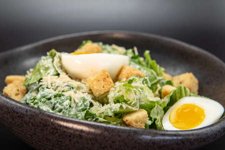 Bowl of Caesar Salad with topped with parmesan cheese, croutons, and hard boiled egg. Reklamní fotografie