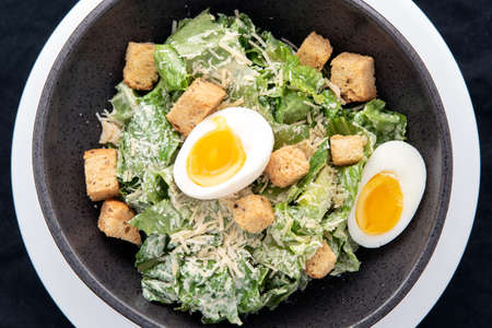 Overhead view of bowl of Caesar Salad with topped with parmesan cheese, croutons, and hard boiled egg.
