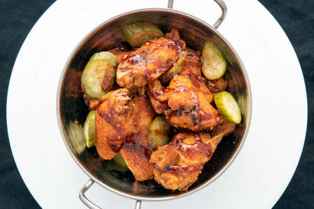 Overhead view of bowl of hot chicken wings and drumsticks for a great spicy flavor.