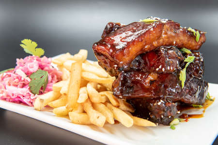 Hearty plate stacked with glazed BBQ pork ribs served with french fries for a plate of finger food.