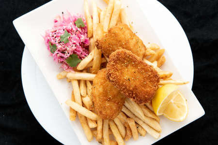 Overhead view of breaded halibut fish and chips served with french fries and lemon garnishment for a plate of delicious finger food.
