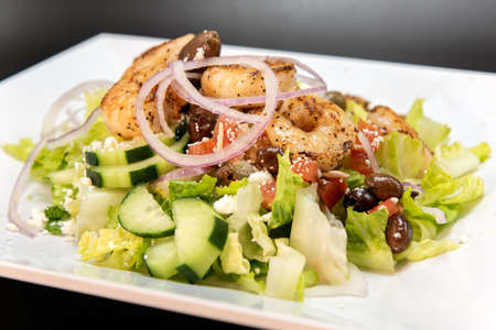 Shrimp Greek Salad stacked high on the plate with healthy vegetables and restaurant quality presentation.