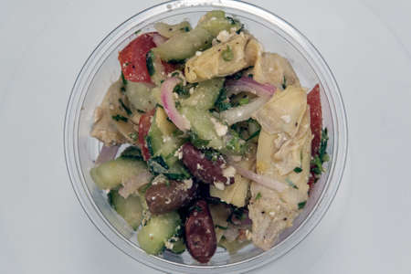 Overhead view of shrimp Greek Salad served by the pound in clear plastic container for presentation of the savory contents.