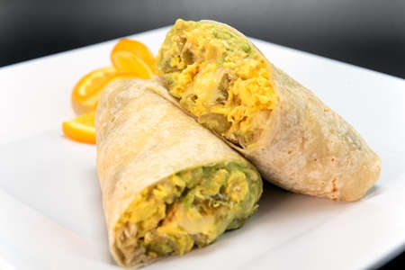 Jack cheese burrito with roasted green chilli, cut in half and stacked on a plate to eat.
