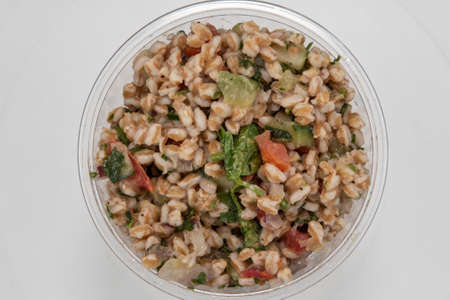 Overhead view of farro grain served by the pound in clear plastic container for presentation of the savory contents.