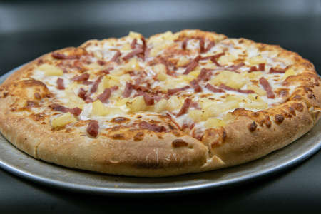 Tangy pineapple tops the Hawaiian pizza with melted cheese for the specialty flavor.