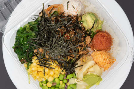 Overhead view of large takeout plastic bowl with three round scoops of poke topped with shrimp tempura, crab meat, edemame, and corn served up and ready to eat.