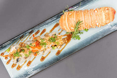 Overhead view of lobster sushi roll with beautiful presentation on the plate including the shell. Фото со стока