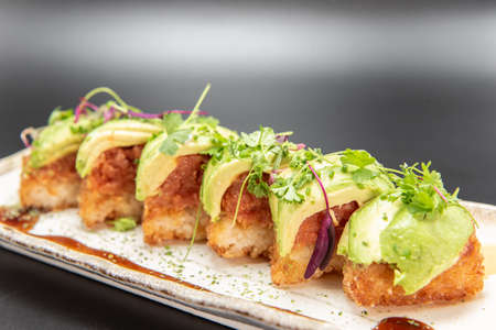Crispy rice pieces topped with spicy tuna and avocado drizzled with spicy mayo and unagi sauce. Фото со стока