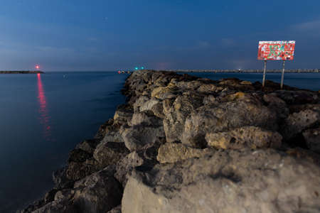 Rocky boulder jetty extends out into the ocean under the dark morning aky with danger sign posted as warning. Фото со стока