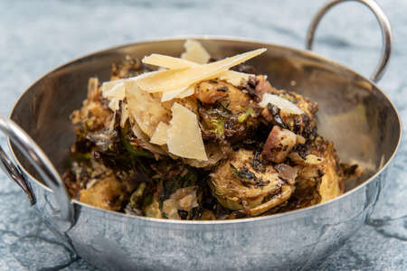 Shiny bowl of roasted brussel sprouts each cut in half and baked to perfection of taste.