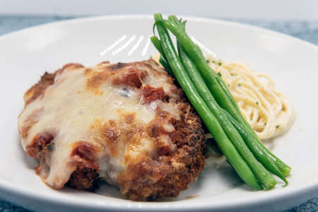 Breaded chicken parmesan served with cheesy pasta and topped with green beans for a delicious dinner meal.