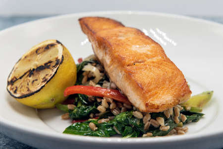 Pan roasted salmon seasoned perfectly on top a pile of barley and garnished with grilled lemon slice.
