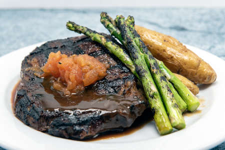 Grilled rib eye steak cooked to perfection served with asparagus, roasted peppers, and topped with a dab of salsa.