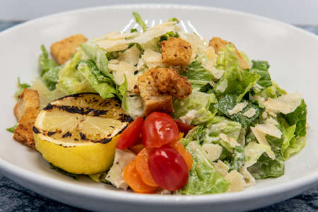 Caesar salad served with a grilled lemon half covered in dressing and presented in a bowl.