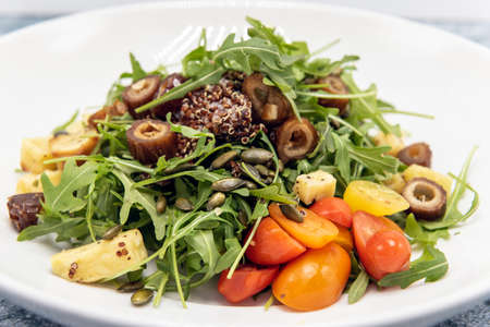 Arugula salad generously piled onto a plate topped with tomatoes and quinoa.