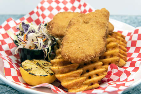 Fish and chips hot of the fryer served with waffle french fries and cole slaw. Фото со стока