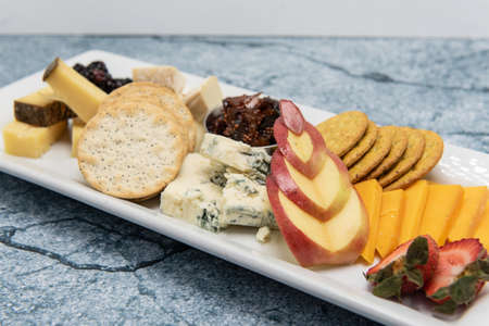 Appetizer plate of assorted cheese, crackers, and fruit decorated with a carved apple for presentation.