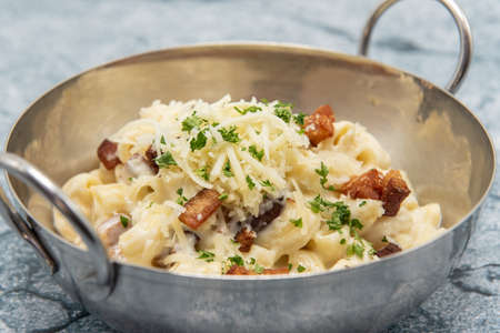 Shiny bowl of macaroni and cheese topped with bits of bacon, parsley, and shredded cheese.
