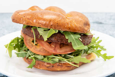 Health conscious vegans can enjoy this vegan burger served with arugula, tomoatoes, and stacked inside a bun Фото со стока