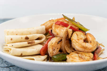 Jumbo pieces of fajita style shrimp piled on stir fry vegetables combined with folded tortillas to eat as a delicious meal.