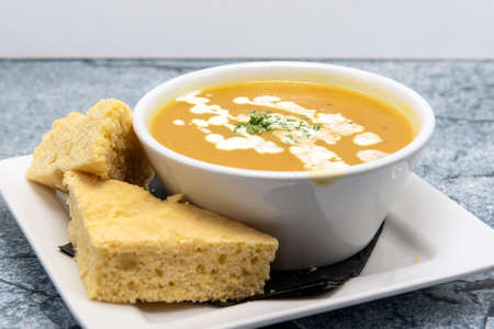 Soup de jour served hot in a bowl with warm slices of cornbread.
