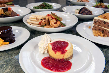 Full table of a variety of restaurant dishes to choose from with New York Style Cheesecake in the center.