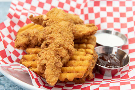 Chicken tenders breaded and cooked to perfection sitting on top of a pile of waffle french fries along with dipping sauces.