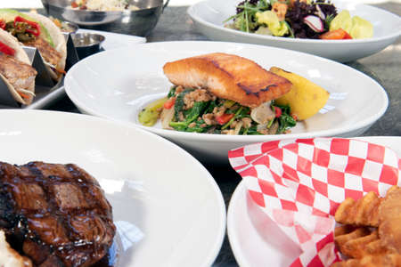 Full table of a variety of restaurant dishes to choose from with pan roasted salmon in the center.