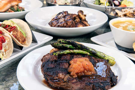 Full table of a variety of restaurant dishes to choose from with rib eye steak in the center.