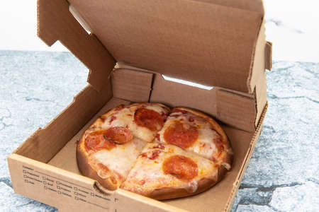 Small personal pan pizza cut into four slices and delivered in cardboard box. Фото со стока