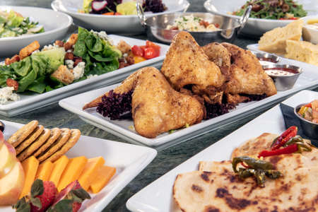 Full table of a variety of restaurant dishes to choose from with roasted chicken wings in the center.