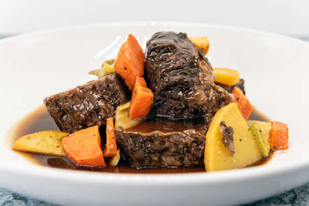 Beef short ribs drenched in a sauce and covered in carrots on other root vegetables.
