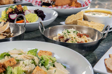 Full table of a variety of restaurant dishes to choose from with macaroni and cheese bowl in the center.
