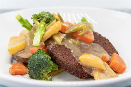 Meatless vegan patty drizzled with gravey and covered with chopped broccoli, carrots, and other mixed vegetables for a delicious vegetatian meal.