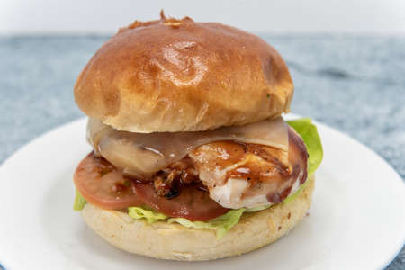BBQ roasted chicken sandwich has melted cheese, tomatoes, lettuce, complete half chicken breast meat.
