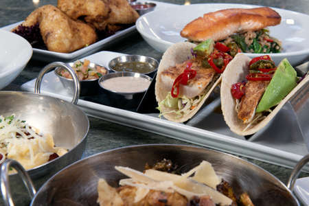 Full table of a variety of restaurant dishes to choose from with pan roasted fish tacos in the center. Фото со стока